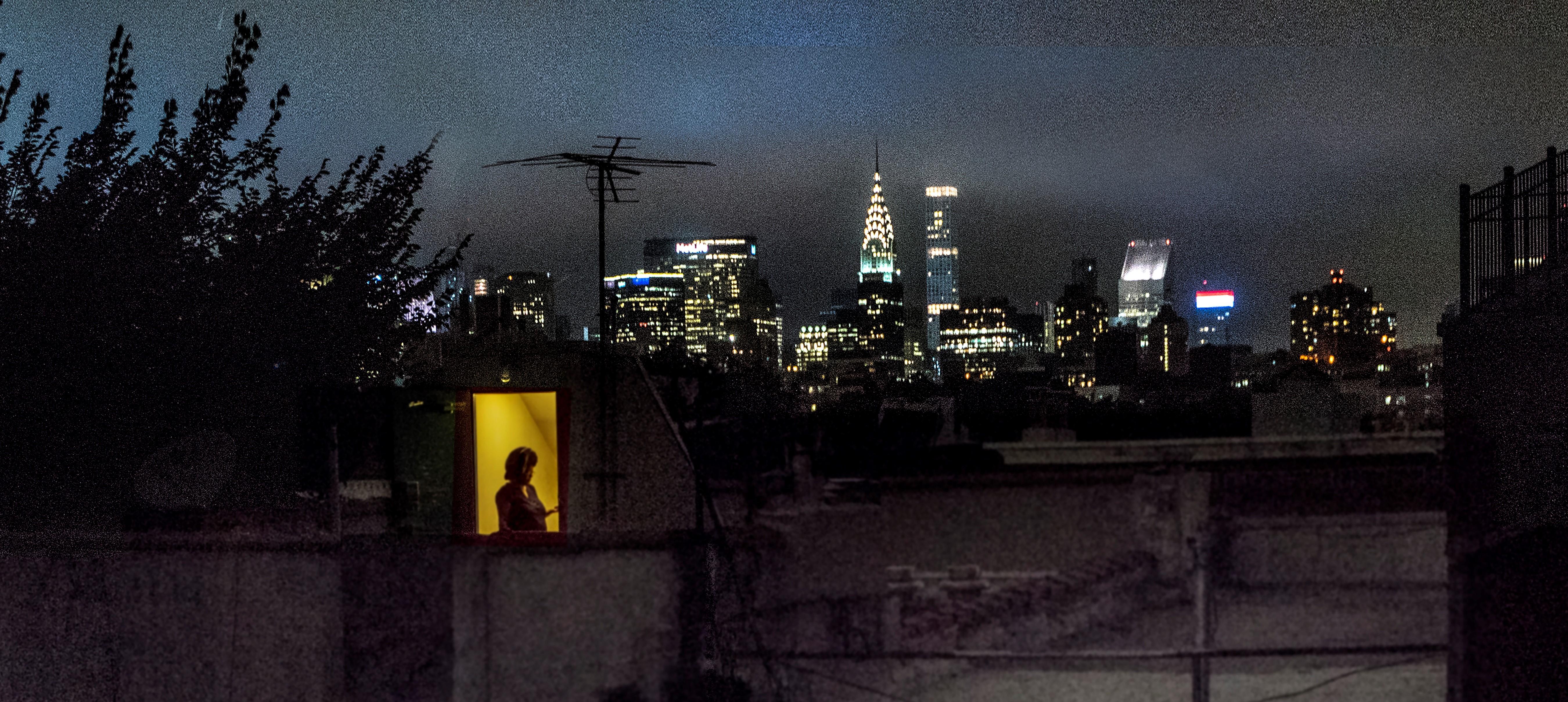 Vue arrière de l'appartement de Sally Davies sur East 5th Street la nuit avec des fenêtres lumineuses.