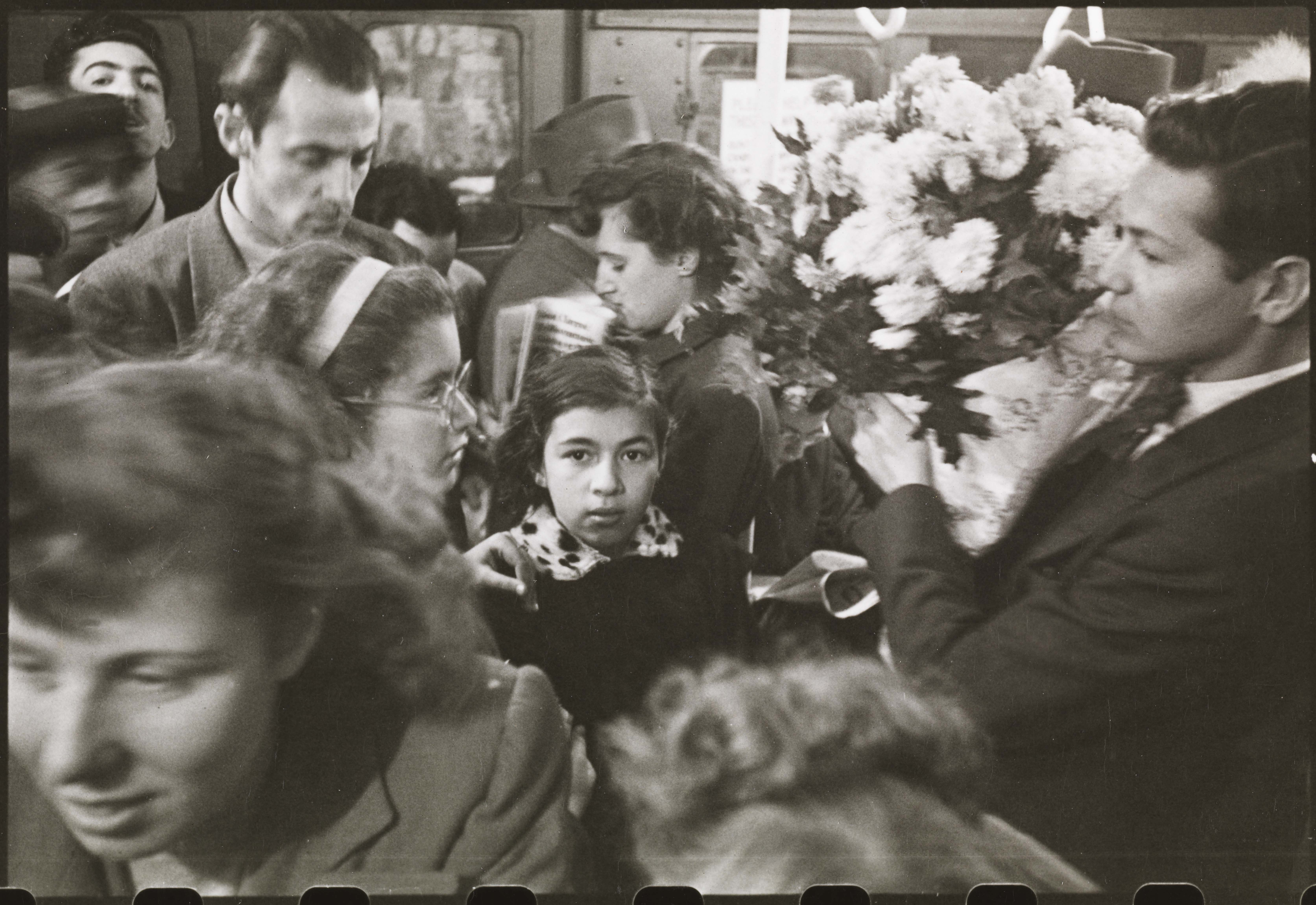 Stanley Kubrick. Life and Love on the New York City Subway. Man carrying flowers on a crowded subway. 1946. Museum of the City of New York. X2011.4.10292.37C