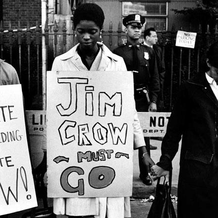 """Una mujer se para en una fila de manifestantes tomados de la mano, con un cartel a su alrededor que dice """"Jim Crow debe irse"""""""