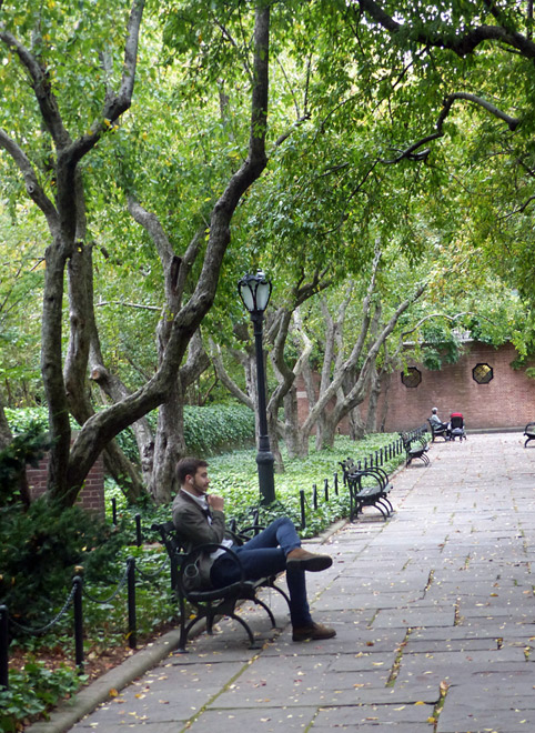 A man sits on a bench under the trees in the Conservatory Garden