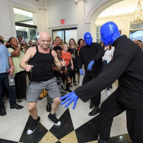 Three Blue Men (from Blue Man Group) dance in the Museum Lobby with visitors during Uptown Bounce in August, 2019.