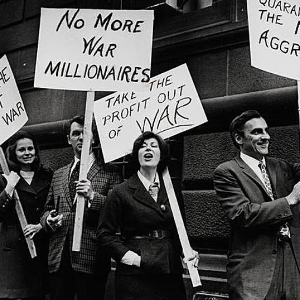 La fotografía en blanco y negro muestra a un grupo de hombres y mujeres que protestan por la participación estadounidense en conflictos en el extranjero. Los manifestantes sostienen carteles que abordan sus preocupaciones.