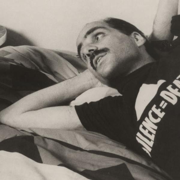 Primer plano de un paciente de SIDA con una camiseta ACT UP y acostado en una cama