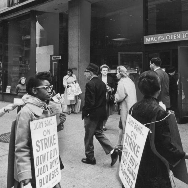 Um grupo de trabalhadores em greve marcham do lado de fora da Macy's enquanto usam cartazes incentivando as pessoas a não comprar blusas de Judy Bond