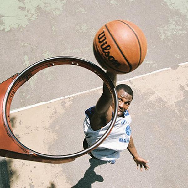Vista desde arriba de un aro de baloncesto sin red, donde se ve a un jugador a punto de tirar una pelota de baloncesto a través del aro