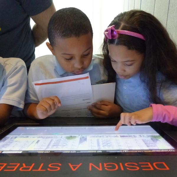 Deux étudiants utilisent un affichage interactif dans les galeries du Musée.