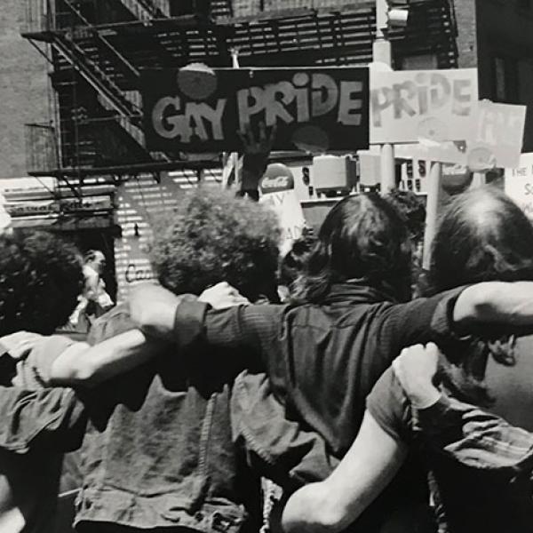 Fotografía de Fred W. McDarrah de un grupo de personas abrazándose y sosteniendo carteles relacionados con Orgullo