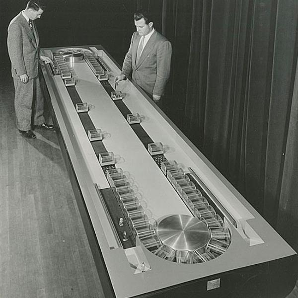 Two men in suits examining a working model of conveyor subway system.