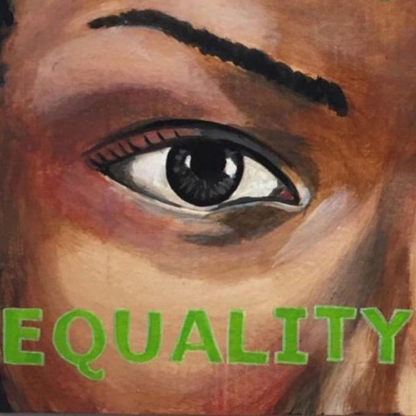 """Primer plano de una pintura del ojo de una mujer, con la palabra """"IGUALDAD"""" escrita en verde debajo de ella"""
