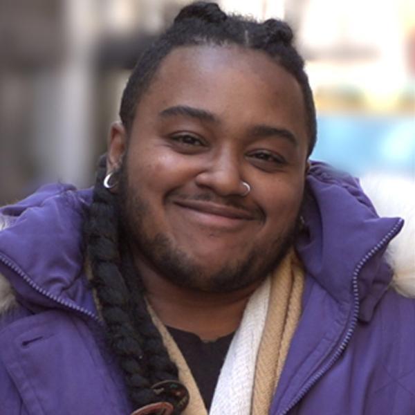 A black American man smiles at the camera