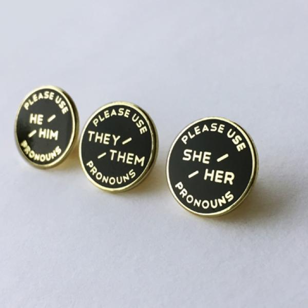 Three enameled pronoun pins. Black background with gold text.