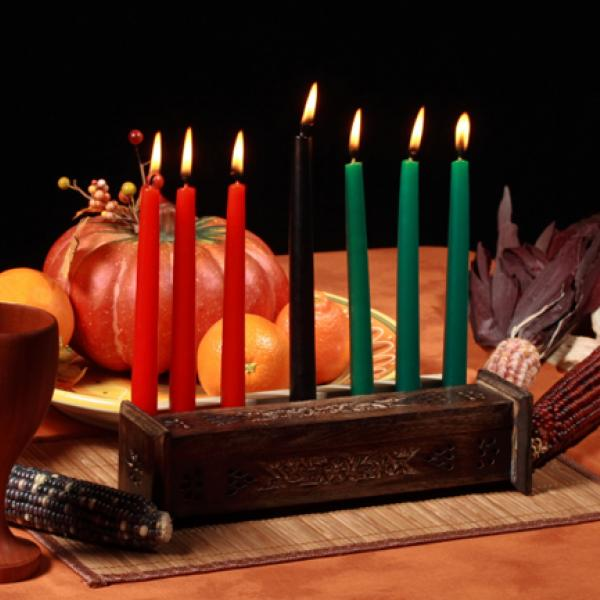 Table set with traditional candle holder, a cup, corn, and gourds.