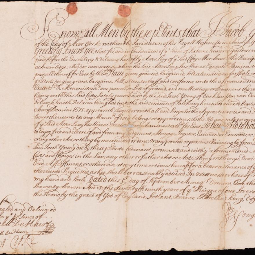 Un viejo trozo de papel con una escritura elaborada y un sello de cera en la esquina inferior derecha.
