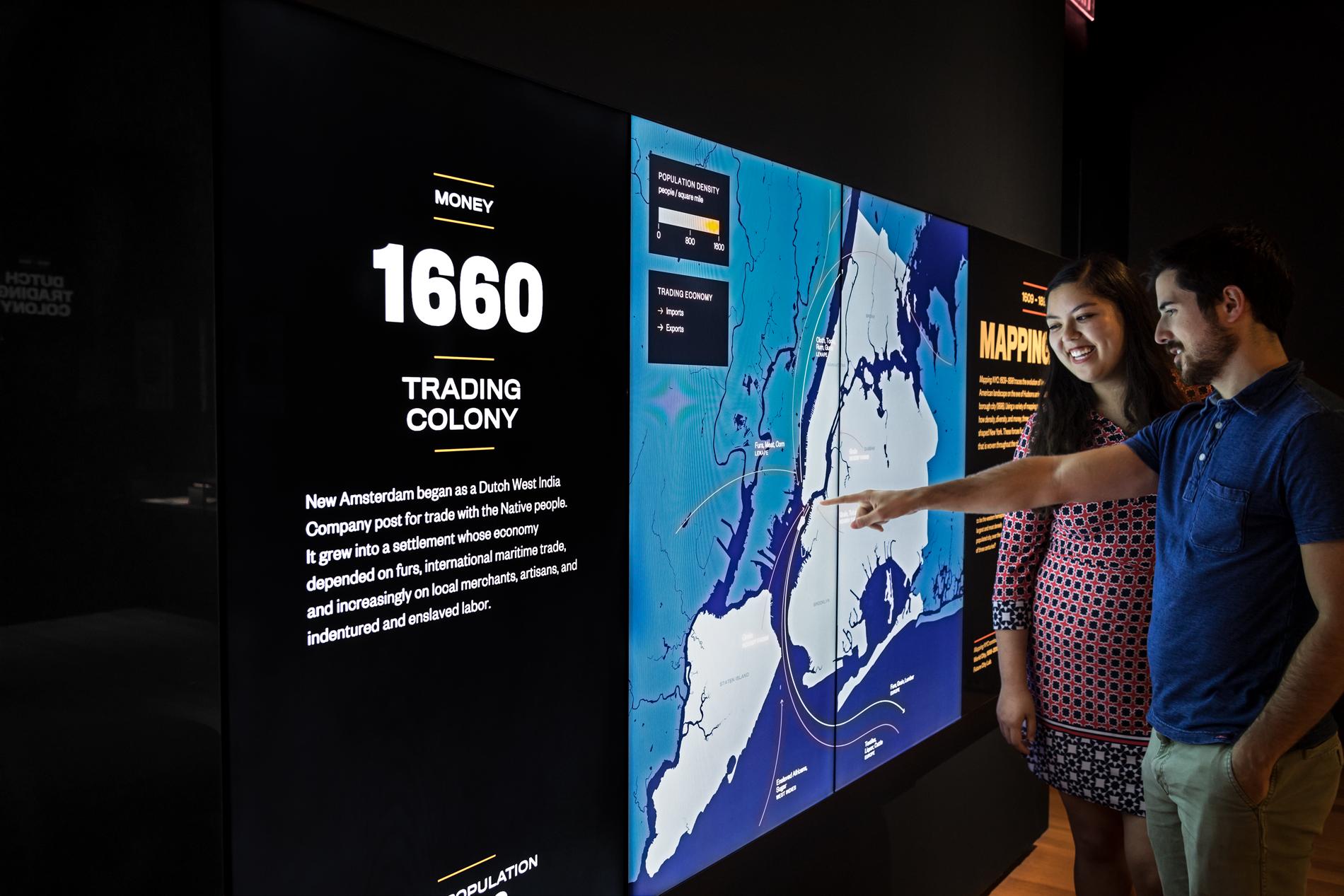 Deux visiteurs indiquent des détails sur un écran dans un espace d'exposition