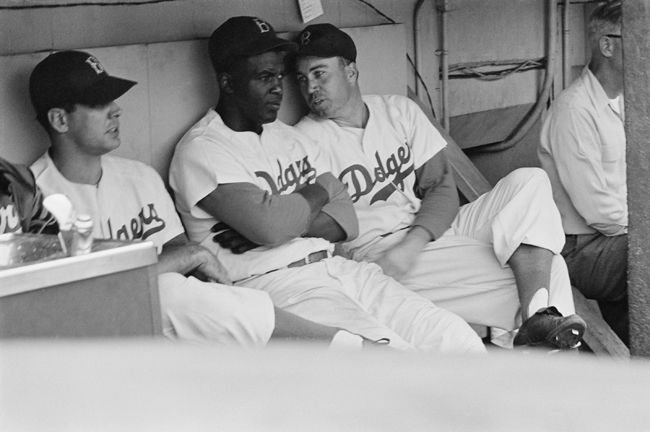 Jackie Robinson has a conversation with teammate Duke Snider in the dugout during a baseball game