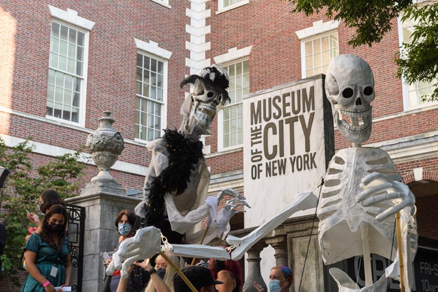 """两个巨大的骷髅傀儡面对面。 在他们身后有一个标有""""纽约市博物馆""""字样的标志。"""