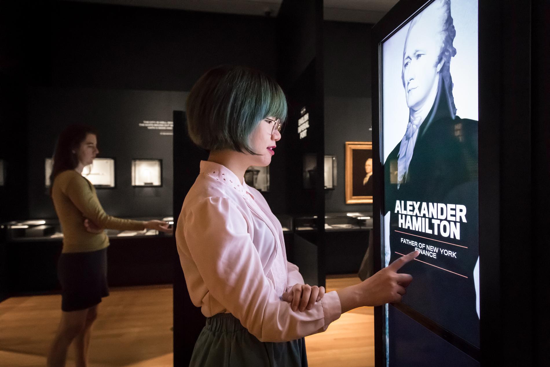两名访客在展览空间中检查互动功能