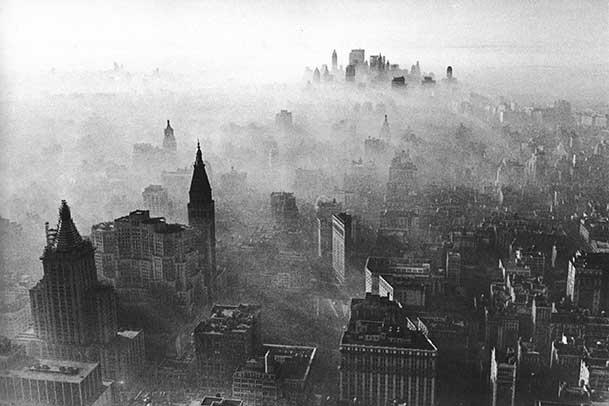 Black and white aerial shot of Midtown and Lower Manhattan. The skyline is obscured by a thick smog.