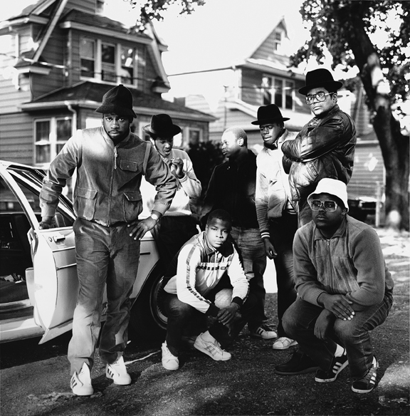 Black and white photograph featuring Run DMC posing in front of a car on a residential street.