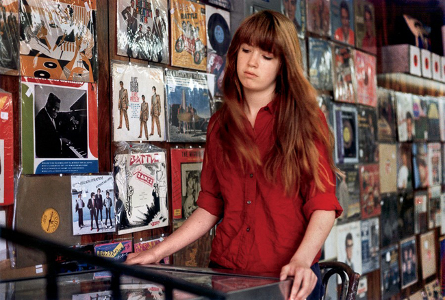Color photograph of a girl in a red shirt sifting through records in a music store.