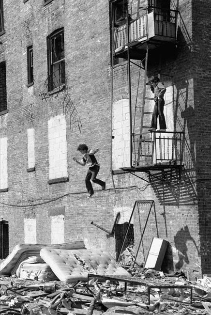Una fotografía de una obra callejera de Martha Cooper de un niño saltando de una escalera de incendios en el Lower East Side.