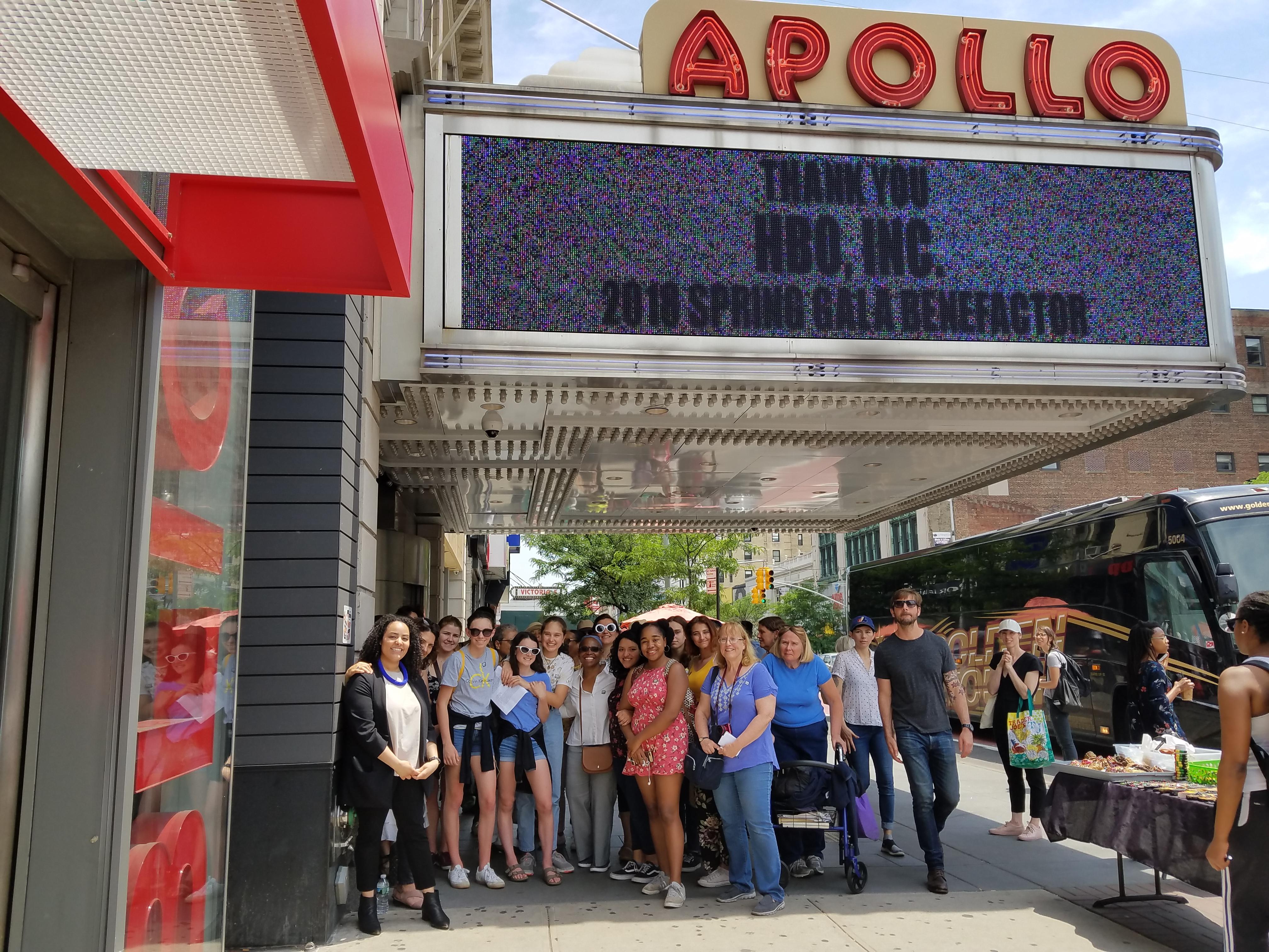 Un groupe de touristes debout sous le chapiteau de l'Apollo Theatre