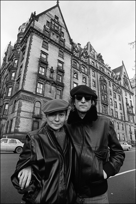 Black and white photo of Yoko Ono, left, and John Lennon, right in front of the Dakota apartment building.