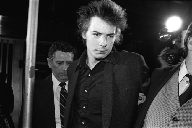 Black and white photograph of Sid Vicious. A man to his left grabs his arm and leads him away.