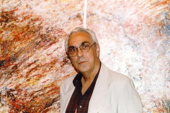 Fotografia colorida de Mario César Romero, vestindo um paletó branco e camisa de botões bordô contra uma parede de mármore marrom