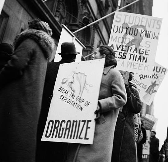 "Photograph depicts models for the garment industry protesting working wages out of the Art Students League. The image is black and white and has protestors holding signs that read ""Organize,"" and ""Break the grip of exploitation"""