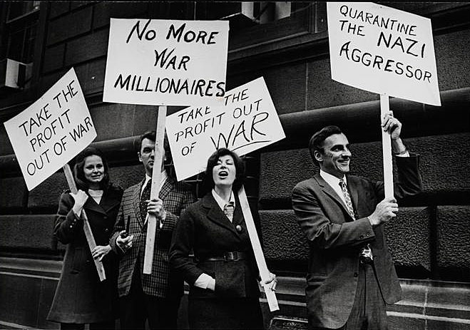 Black and white photograph depicts a group of men and women protesting American involvement in conflicts abroad. Protestors are holding signs addressing their concerns.