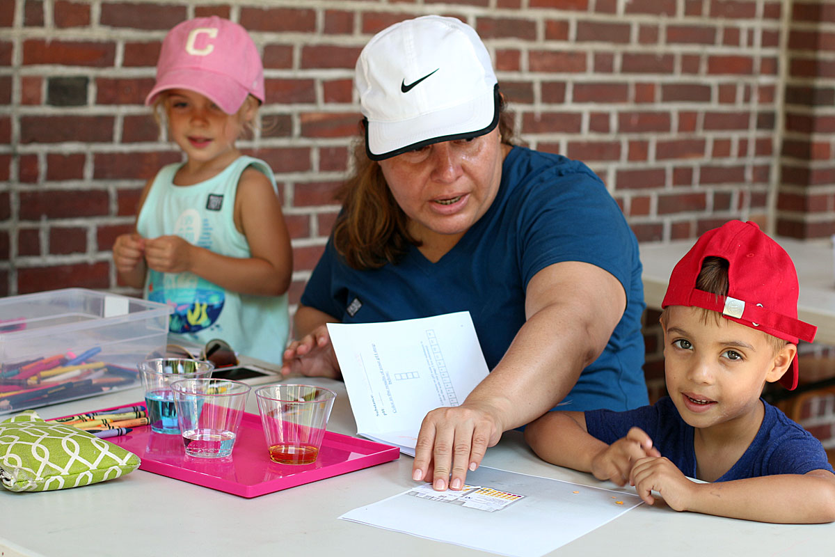 Photograph of a family participating in a wet water lab, involving the testing varying pH levels of different liquids.