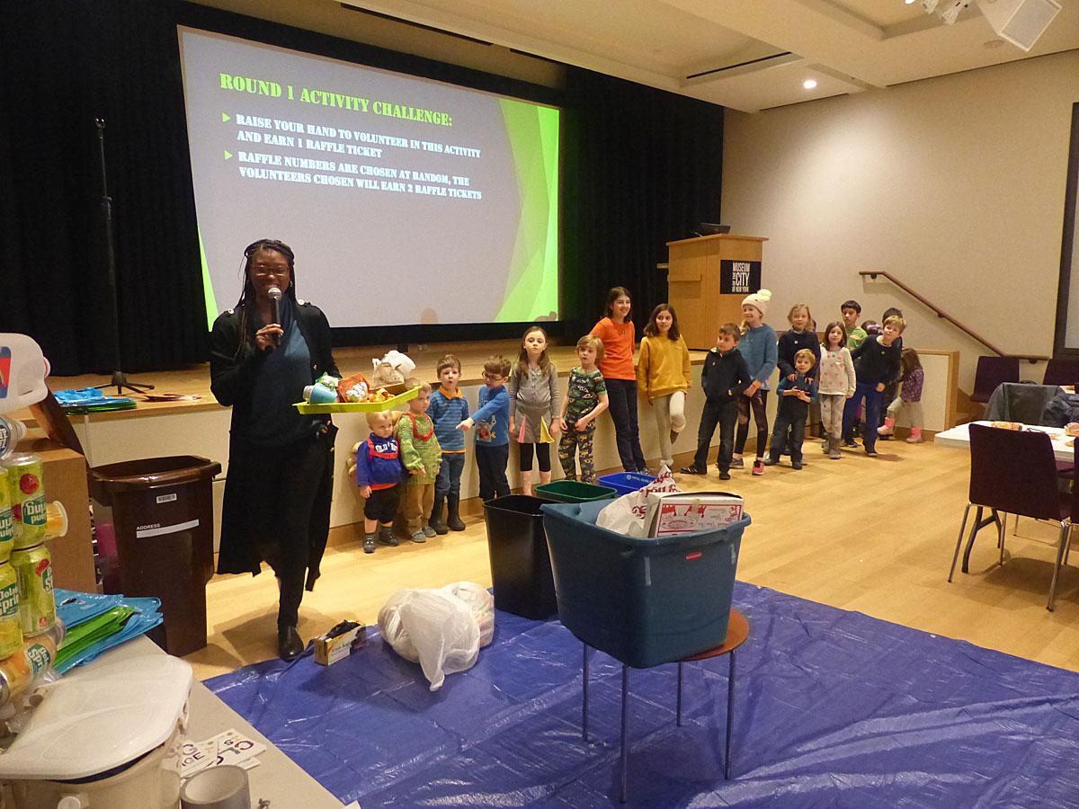 재활용 가능한 재료를 기준으로 폐기물을 적절한 쓰레기통으로 분리하는 참가자 사진.