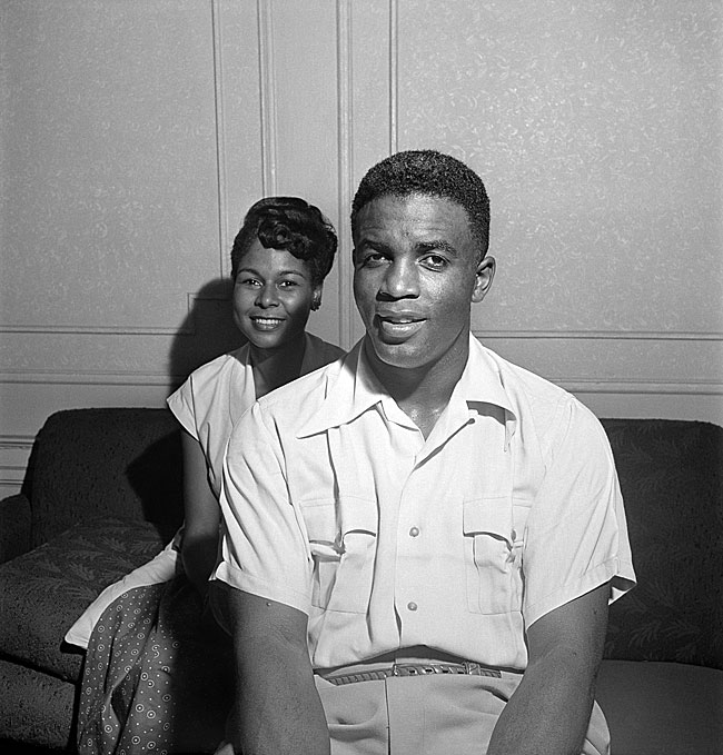 Black and white photograph from Look magazine that features Jackie and Rachel Robinson in their home. The couple are seated on a couch inside their apartment.