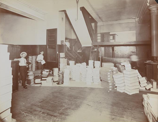 Interior of Rogers Peet & Co. store stock room with two men working and boxes stacked all around.