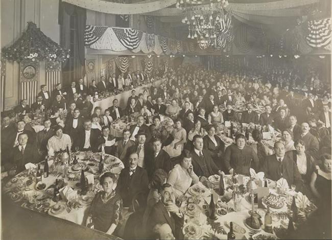 Fotografía en blanco y negro alrededor de 1910 de un banquete formal. Hombres, mujeres y algunos niños se sientan en las mesas mirando a la cámara, los cubiertos, los postres y las botellas de vino son visibles en las mesas.