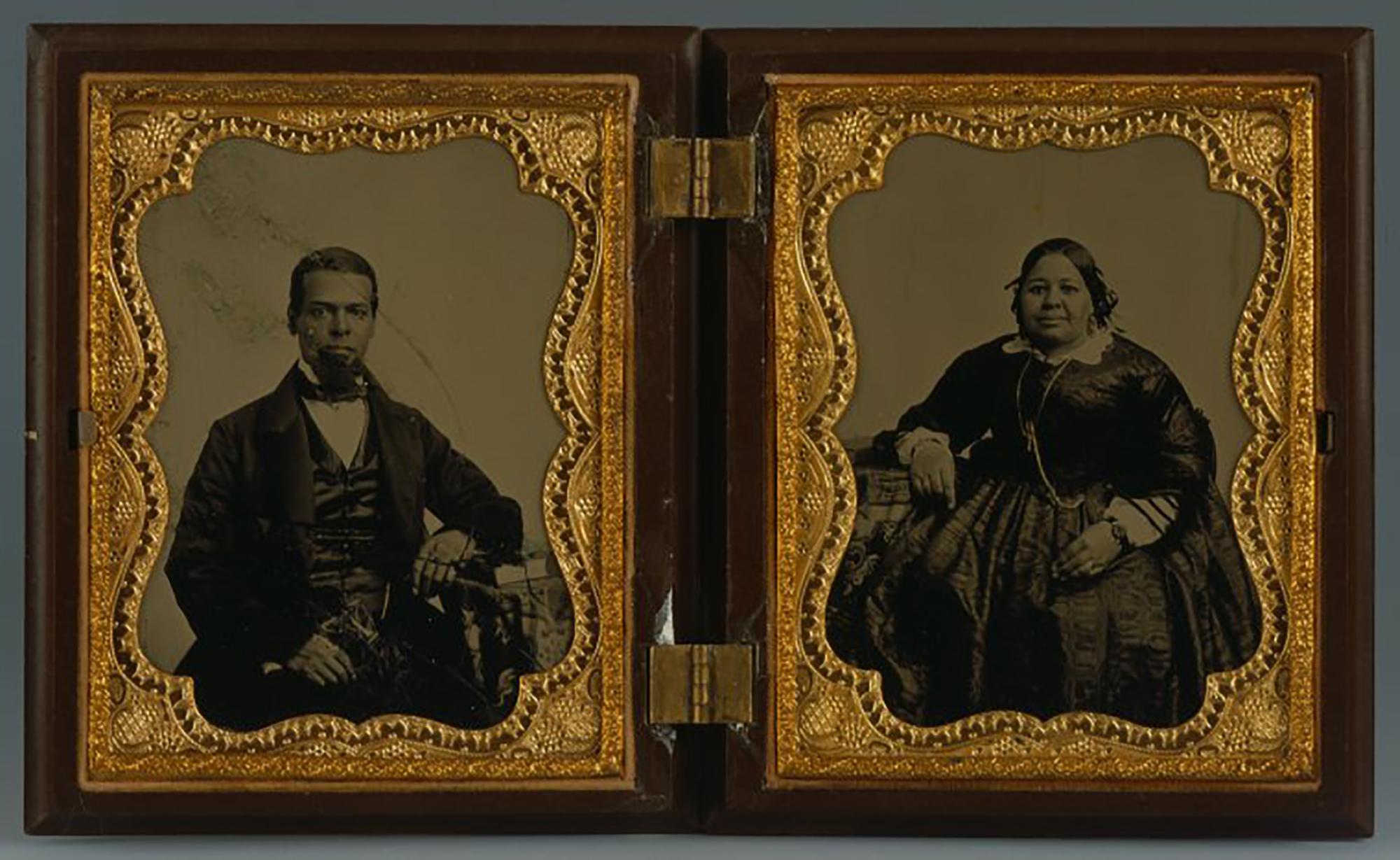 Duas fotografias em preto e branco em uma caixa de madeira com dobradiças e ouro. O homem, à esquerda, e a mulher, à direita, são negros e usam um vestido e terno escuro da moda.