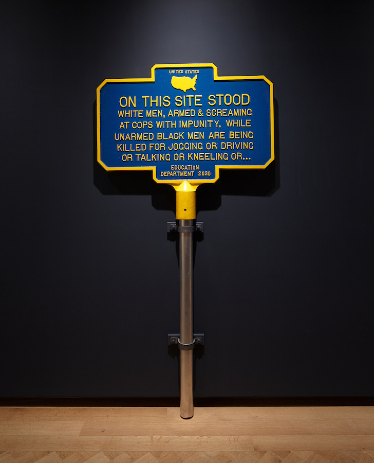 Blue and yellow metal sign in the style of historic landmark signs that marks the racial justice uprisings that took place during 2020.