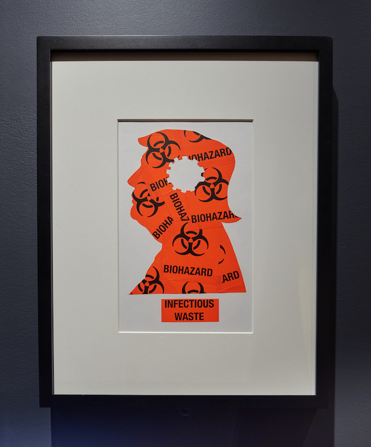 A matted, framed print that depicts a profile of Donald Trump created out orange biohazard labels.