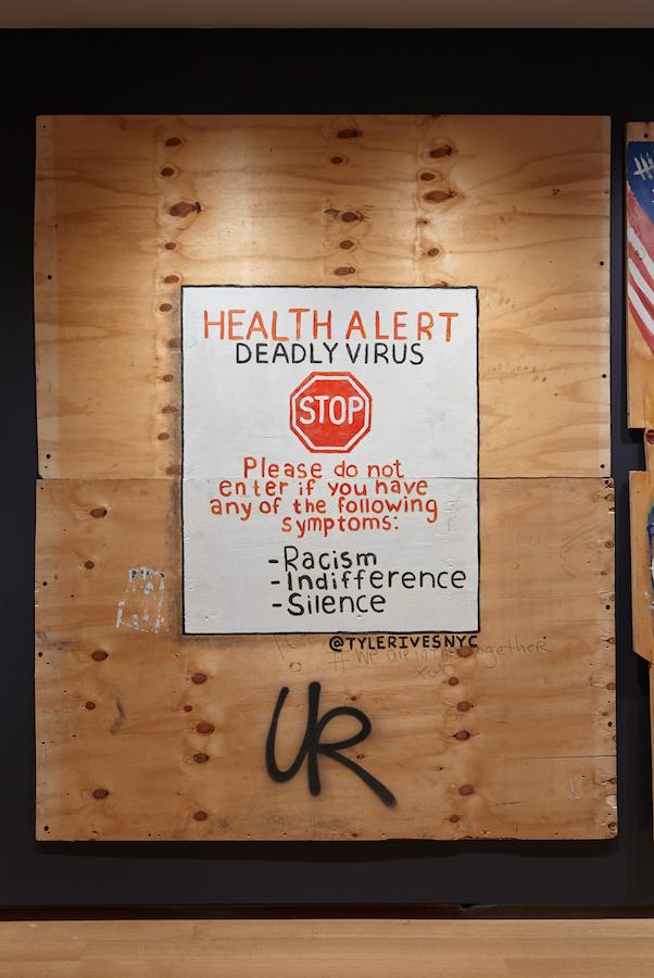 Illustration en contreplaqué créée lors de la pandémie COVID-19 et des soulèvements de la justice raciale en 2020. Un panneau blanc est peint au centre du bois avec des lettres rouges et noires et un symbole de panneau d'arrêt.