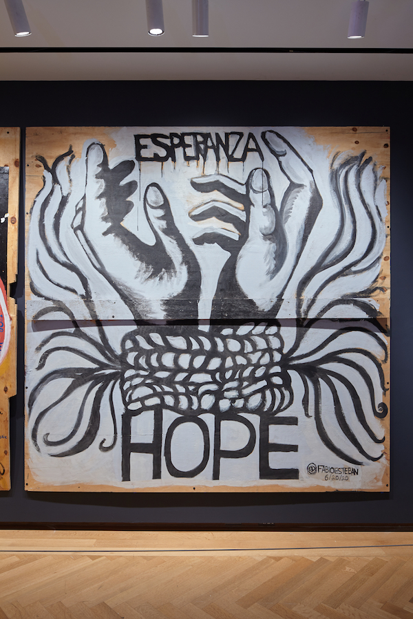"Plywood artwork created during the COVID-19 pandemic and racial justice uprisings in 2020. Bound hands, lined in black against a white background, reach upward. The words ""Esperanza"" and ""Hope"" appear above and below."