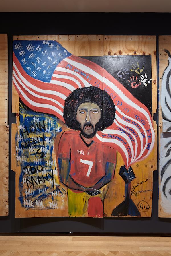 Illustration en contreplaqué créée lors de la pandémie COVID-19 et des soulèvements de la justice raciale en 2020. Colin Kaepernick est au premier plan, à genoux pliés, avec le drapeau américain flottant derrière lui.