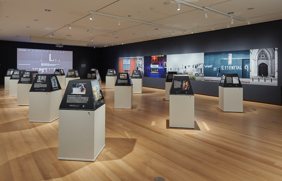 Installation Shot of New York Responds: The First Six Months. View of the main exhibition space with 15 plinths holding objects and images, and some images visible on the walls.