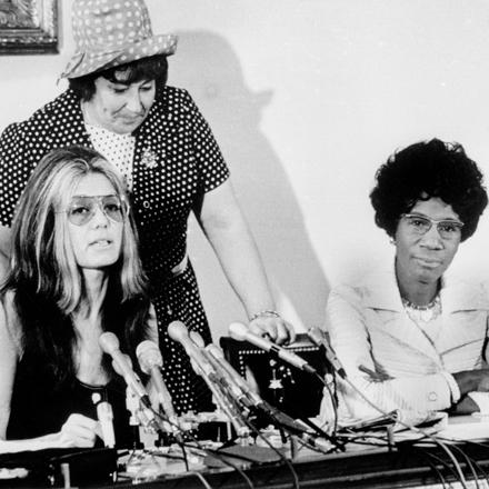 Tres mujeres se sientan en una mesa, una tiene micrófonos frente a ella, lo que sugiere que es una conferencia de prensa.