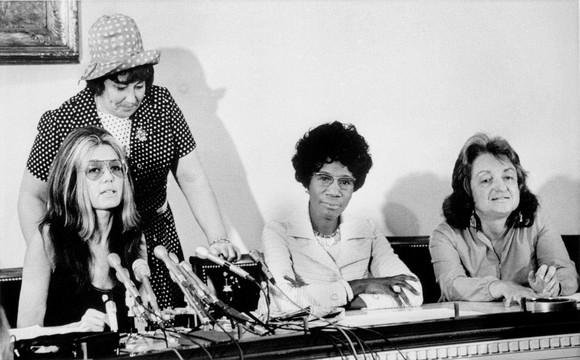 세 명의 여성이 테이블에 앉아 있고, 한 명의 여성이 그녀 앞에 마이크를 가지고 있으며, 이는 기자 회견임을 시사합니다