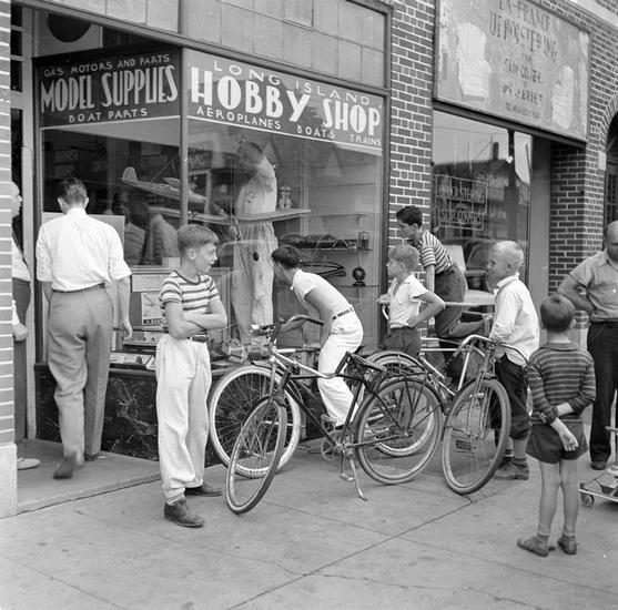 Group of youths on bicycles looking into the window of a Hobby Shop selling airplanes and train models.
