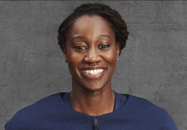 Tina Charles head shot - gray background with blue shirt