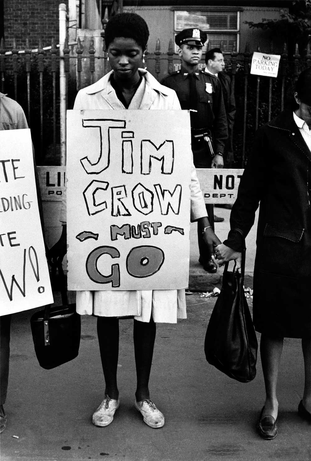 "A woman stands in a line of protesters holding hands, with a sign around her that says ""Jim Crow must go"""