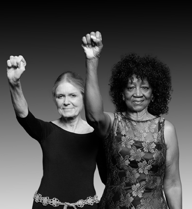 Gloria Steinem and Dorothy Pitman Hughes stand next to each other, each raising one arm with a closed fist.