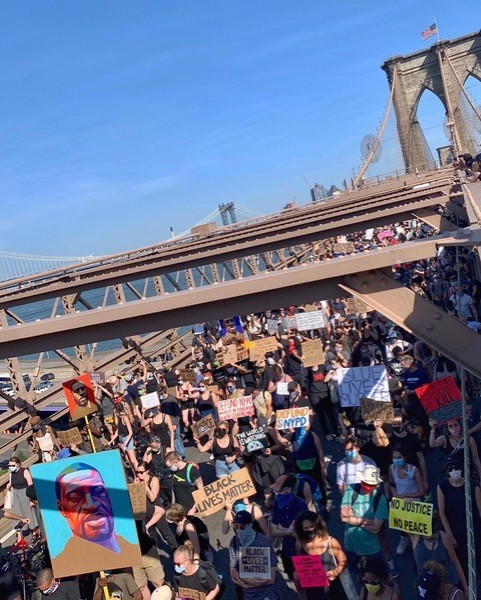 A group of protesters on the Brooklyn Bridge with various signs.